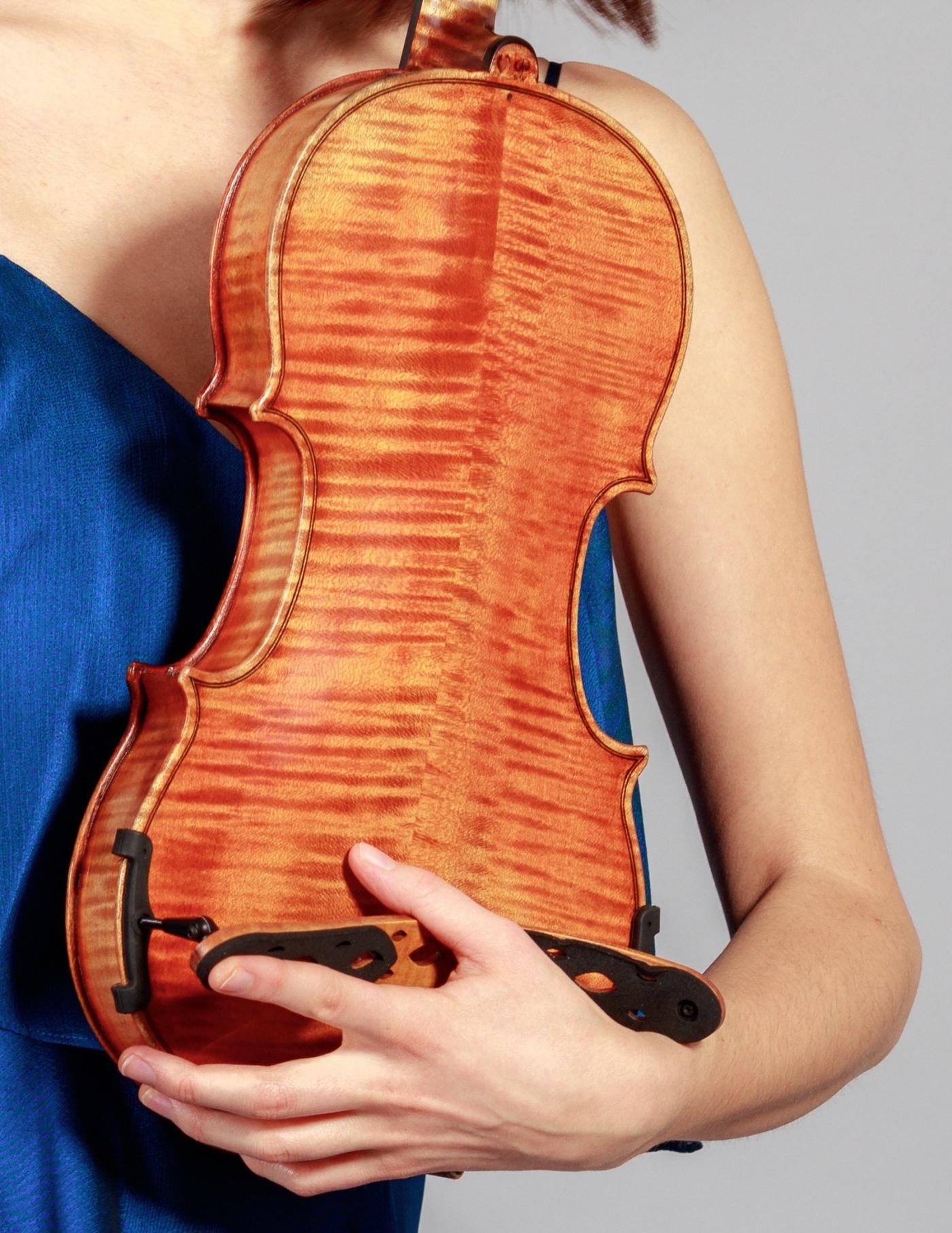 Junge Frau hält eine Violine im Arm